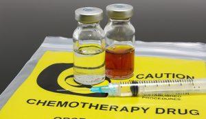 Ein Fläschchen mit einer durchsichtigen Lösung und ein Fläschchen mit einer braunen Lösung liegen neben einer Spritze auf einer Tüte mit der Aufschrift Chemotherapy Drug