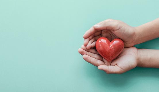 Herz aus Glas in zwei Händen