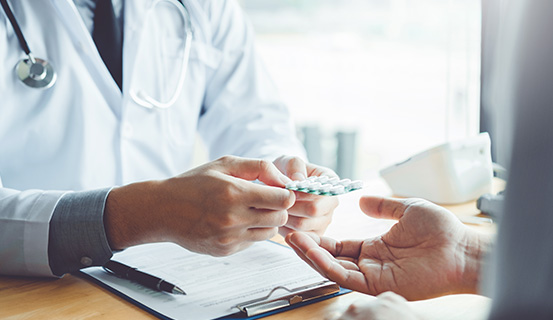 Arzt überreicht Patient Tabletten