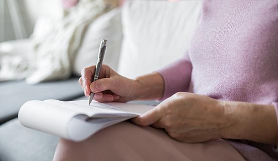 Eine Frau sitz auf einem Sofa und füllt einen Fragebogen aus, der auf ihrem Schoß liegt.