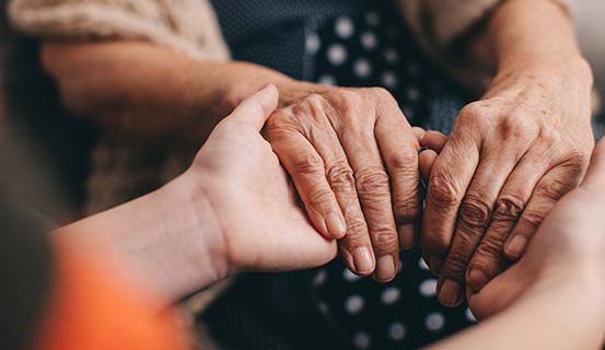 Eine Frau legt ihre Hände in die Hände einer anderen Person