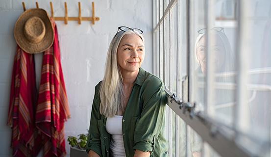 Frau sitzt lächelnd vor einem Fenster und schaut hinaus