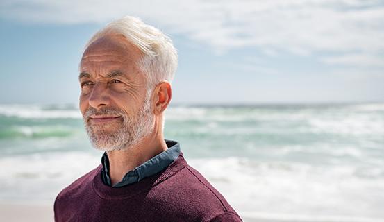Älterer Mann steht am Meer und lächelt