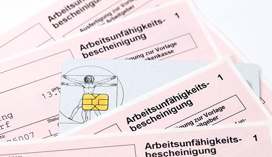 Eine Versicherungskarte zwischen mehreren Arbeitsunfähigkeitsbescheinigungen