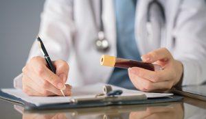 Ärztin hält ein Blutabnahmeröhrchen in der Hand und schreibt etwas auf