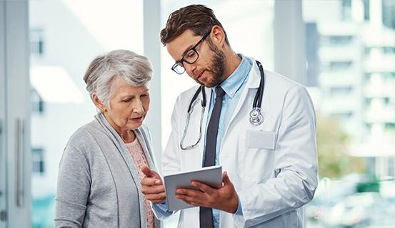 Arzt zeigt Patientin etwas auf einem Tablet