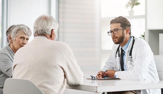 Ein Arzt sitzt mit einem Mann und einer Frau an einem Tisch