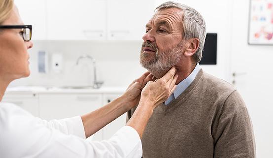 Ärztin tastet den Hals eines Patienten ab