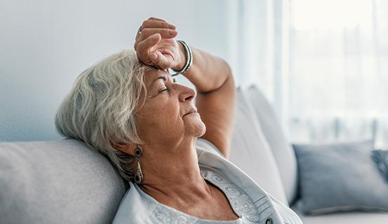 Ältere Frau liegt erschöpft auf dem Sofa