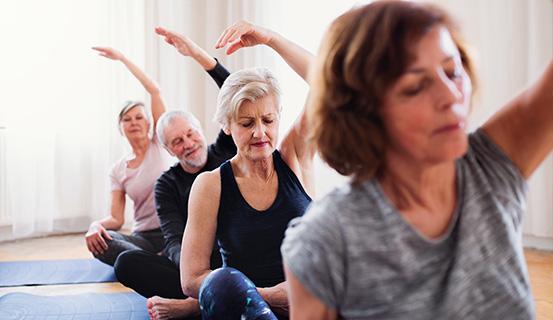 Vier Erwachsene machen Yoga