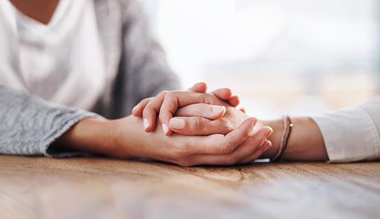 Frau hält die Hände einer anderen Frau fest